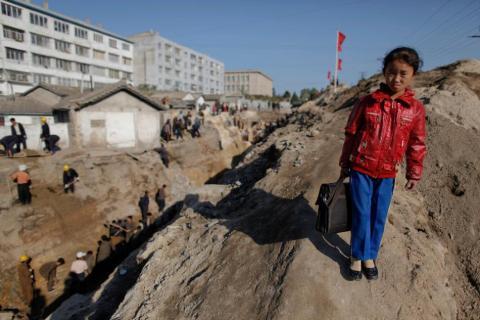 Una colegiala camina mientras estudiantes y voluntarios trabajan para reparar el sistema de suministro de agua en Haeju (Corea del Norte), que sufrió daños a raíz de las inundaciones y tifones de octubre de 2011.