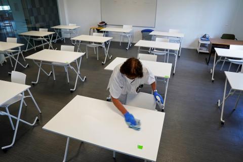 Una limpiadora desinfecta las mesas de un aula en un colegio de San Sebastián, que reabrirá la semana que viene tras la pandemia del coronavirus