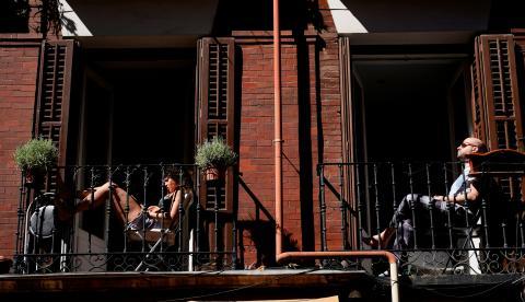 Madrileños toman el sol en las terrazas de sus pisos durante el confinamiento