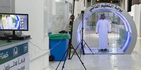 Un hombre pasa a través de una puerta de auto-esterilización en una entrada de la Kaaba y la Gran Mezquita, la Meca, el 8 de mayo de 2020.