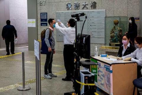 Se controla la temperatura de un hombre antes de ingresar a un edificio de oficinas gubernamentales en Hong Kong el 2 de marzo de 2020