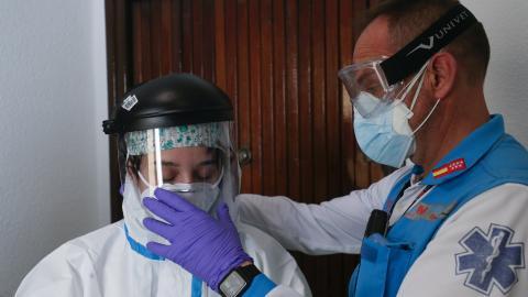 Unos sanitarios se ponen una mascarilla para atender a una persona con coronavirus.