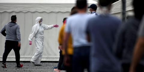 Personal médico haciendo gestos mientras empleados de la comercializadora de carne Westfleisch esperan en fila para hacerse la prueba del coronavirus en un centro de pruebas provisional en Hamm, Alemania, el 10 de mayo de 2020.