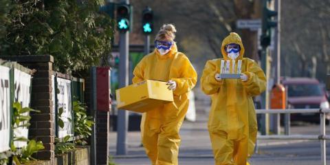 Voluntarios médicos caminando hacia una consulta médica después de tomar muestras.