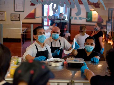 Servers wearing gloves and masks get takeout orders from the kitchen at a restaurant in Houston, Texas, on May 1.