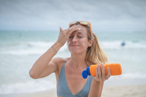 Una mujer se aplica protector solar en el rostro.