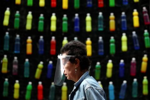 Una mujer pasea por Madrid con una pantalla facial para protegerse del coronavirus.