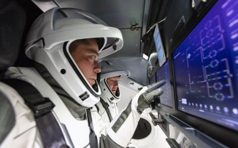 Los astronautas de la NASA Bob Behnken (primer plano) y Doug Hurley (segundo plano) se entrenan dentro de la nave espacial SpaceX's Crew Dragon.