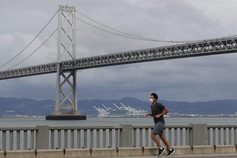 Un hombre con mascarilla corre por el Embarcadero en San Francisco.
