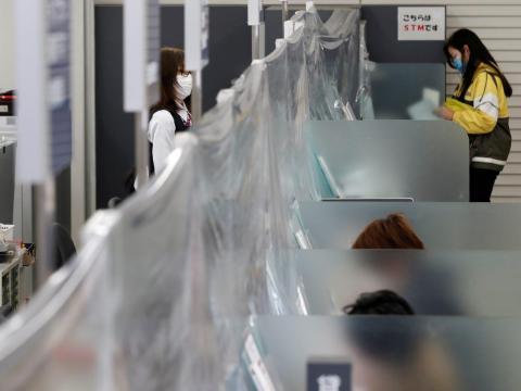 Trabajadora de un banco con mascarilla en un mostrador con una cortina de plástico instalada en la sucursal de Higashinakano del Banco MUFG en Tokio, Japón, el 24 de abril de 2020.
