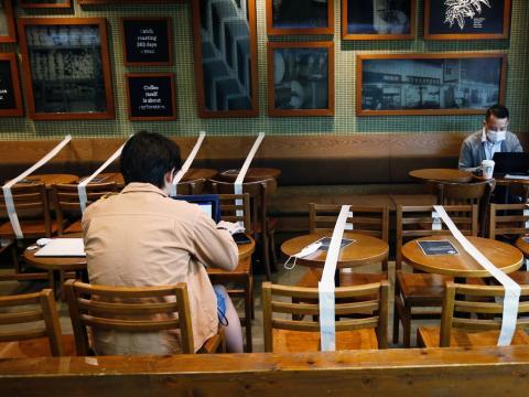 Mesas y sillas con cinta adhesiva para mantener el distanciamiento social en una cafetería Starbucks en Hong Kong, el 2 de abril de 2020.