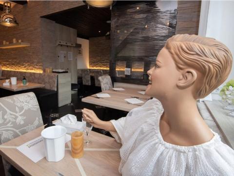 La muñeca, un letrero y una cinta adhesiva, indican que ningún cliente puede sentarse ahí.