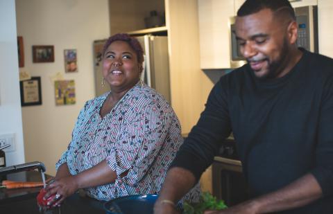 Pareja riéndose en la cocina.
