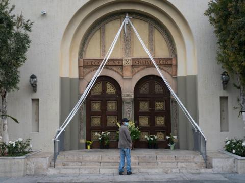 Un feligrés reza fuera de la cerrada Iglesia de Cristo Rey Iglesia Católica Romana en Los Ángeles el 12 de abril de 2020.