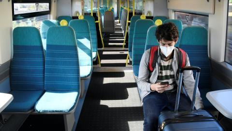 Un pasajero de tren mira su móvil al llegar a la estación de Londres en plena pandemia de coronavirus.