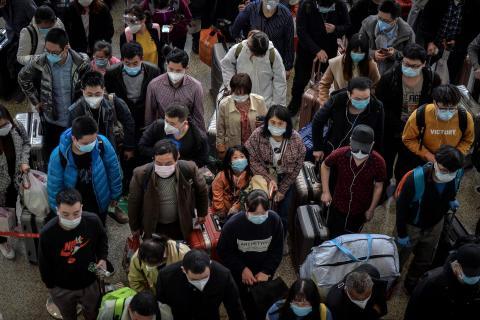 Pasajeros esperan para pasar las puertas de embarque en la estación de tren de Hankou en Wuhan, China, 8 de abril de 2020.