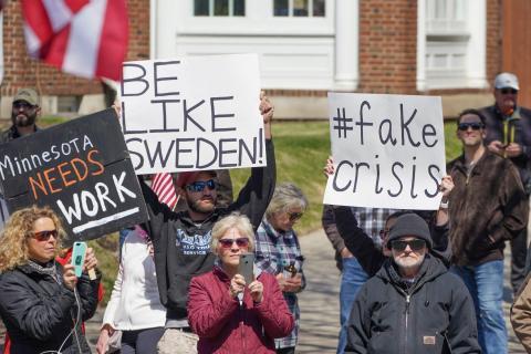 """La gente protesta contra la orden de quedarse en casa de Minnesota con un letrero de """"Sé como Suecia"""" frente a la residencia del gobernador el 17 de abril de 2020."""