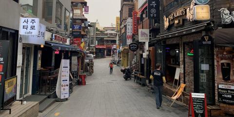 La gente camina por una calle vacía en Itaewon, Seúl, Corea del Sur, después de que los bares y clubes volvieran a cerrarse, el 14 de mayo de 2020.