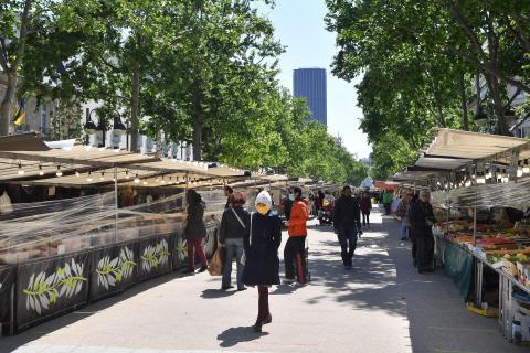 Personas con mascarillas caminan por el mercado de Saxe-Breteuil junto a la torre de Montparnasse el 14 de mayo de 2020, en París, Francia.