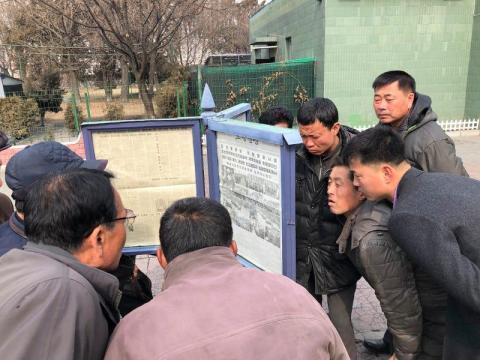Los hombres se reúnen alrededor de las publicaciones del periódico público para leer sobre la visita del líder norcoreano Kim Jong Un a Vietnam.