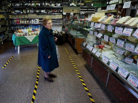 Una señora espera a ser atendida tras las líneas amarillas que marcan la distancia que los clientes deben mantener, en Roma, Italia, el 10 de marzo.