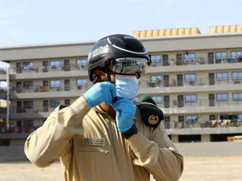 Un oficial de policía lleva un casco inteligente puesto para comprobar la temperatura de los trabajadores durante el brote de la enfermedad coronavirus (COVID-19) en Dubái.