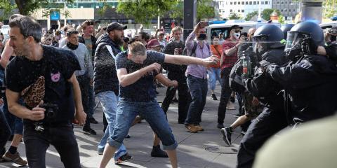 Oficiales de policía rocían con gas pimienta a manifestantes en Berlín, Alemania, el 9 de mayo de 2020.