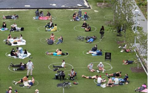 Varios grupos de personas distanciadas en Domino Park (Williamsburg, Brooklyn, Nueva York).