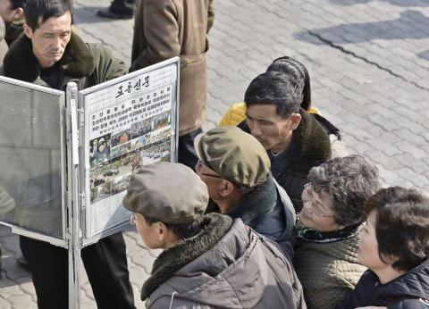 Los hombres se reúnen alrededor de las publicaciones del periódico público en Pyongyang en Pyongyang.
