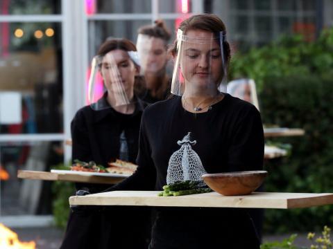 Camareros con equipo de protección sirven la comida en un restaurante en Amsterdam el 5 de mayo de 2020.