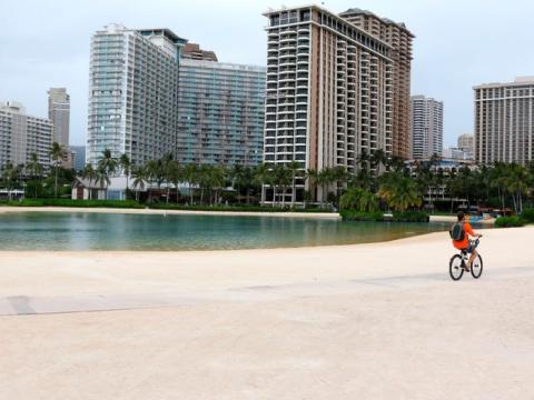En esta foto del 21 de abril de 2020, un hombre monta su bicicleta en la playa de Waikiki en Honolulu.
