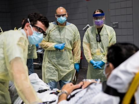 Soldiers assigned to the Javits New York Medical Station conduct check-in procedures on an incoming coronavirus patient with local emergency workers in New York City, April 5, 2020.