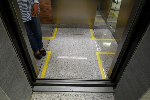 Áreas marcadas para delimitar las distancias entre personas en un ascensor de un edificio de oficinas en Singapur el 31 de marzo de 2020.