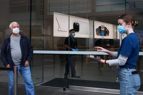 Staff members assist customers prior to entering the Bondi Junction Apple Store by limiting the number of visitors in the store at one time.