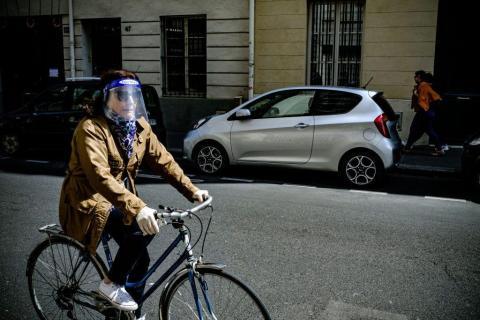 Una mujer con pantalla de protección pasea en bici.