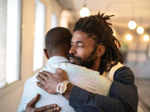 Men hugging.