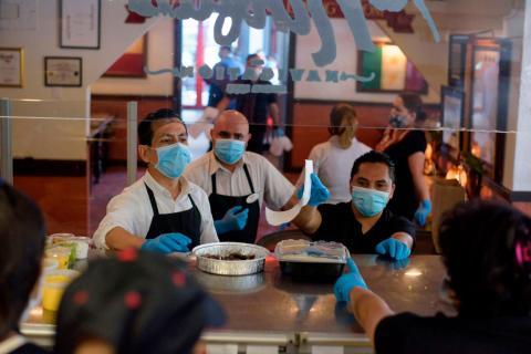 Varios empleados de un restaurante en Texas llevan equipos de protección para servir a los clientes.