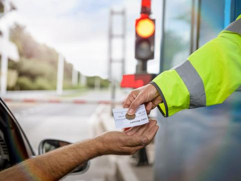 A driver paying a toll.