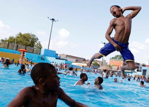 Unos niños nadan en una piscina pública.