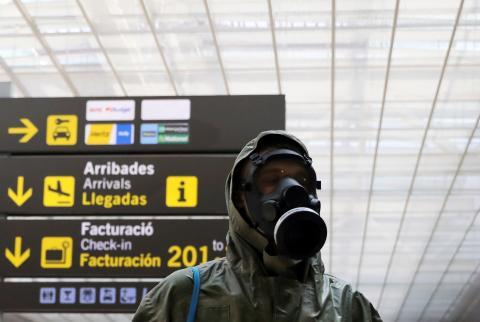 Un viajero equipado con máscara de gas y traje protector en el aeropuerto de El Prato durante el confinamiento por el coronavirus