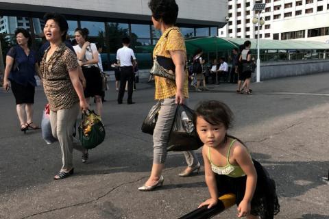 Una niña juega con una barra de seguridad de un aparcamiento situado frente a unos grandes almacenes en Pyongyang.