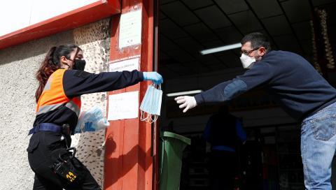 Una voluntaria de Protección Civil reparte mascarillas en una empresa de Ronda (Málaga)