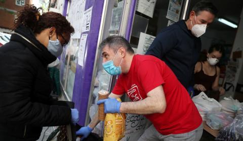 Voluntarios reparten comida a familias sin recursos en la asociación de vecinos de Aluche (Madrid)