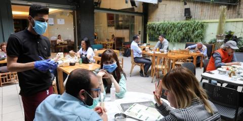 Un camarero tomando nota de un pedido en la terraza exterior de un restaurante en Beirut, Líbano, el 11 de mayo de 2020, después de la reapertura del país.