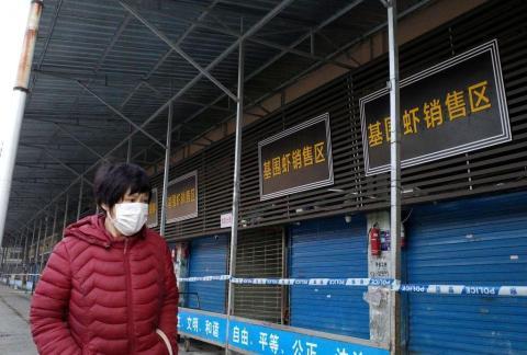 Una mujer camina frente al mercado callejero de  Huanan cerrado el 12 de enero de 2020.