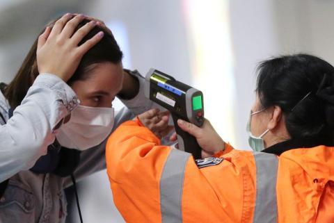Un trabajador verifica la temperatura de un pasajero que llega al aeropuerto internacional de Hong Kong con un termómetro infrarrojo en febrero de 2020