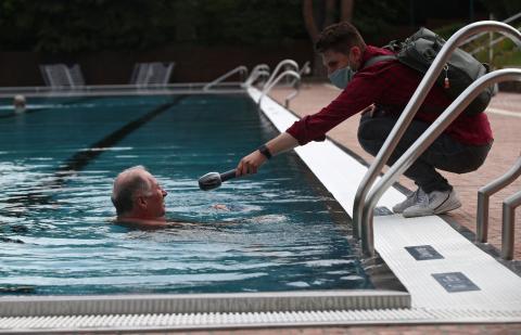 Un bañista da una entrevista desde la piscina durante el coronavirus.