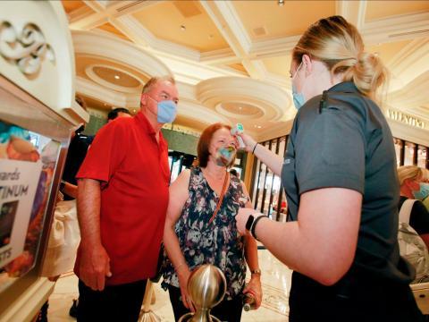 Un empleado del Hotel y Casino Bellagio toma la temperatura a una pareja el 4 de junio de 2020.