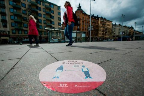 Una señal de los servicios de atención médica de Suecia en el suelo del centro de Estocolmo para indicar a las personas que mantengan la distancia de seguridad.