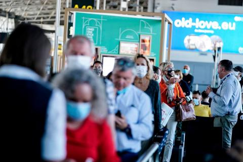 Passengers queue at the boarding gate at Brussels Airport, in Zaventem, on June 15, 2020 as Brussels Airport reopens for travels within Europe and the Schengen zone, after a months-long closure aimed at stemming the spread of the COVID-19 pandemic, caused